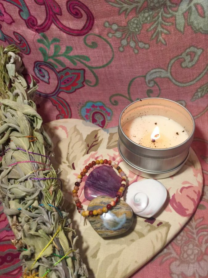 A set up consisting of (from left to right) a sage bundle, a jasper healing stone bracelet, three heart-shaped crystals, and a candle.