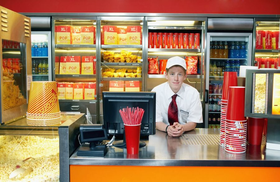 A visual example of a teenage boy working at a movie theater food counter.