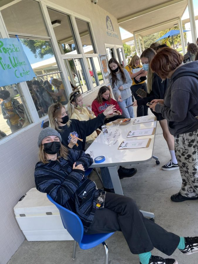 Oct. 19 2021, during lunch Senior Grace Hurguy poses for camera while  passing out surveys in exchange for Popsicles for the wellness center with other wellness leaders.