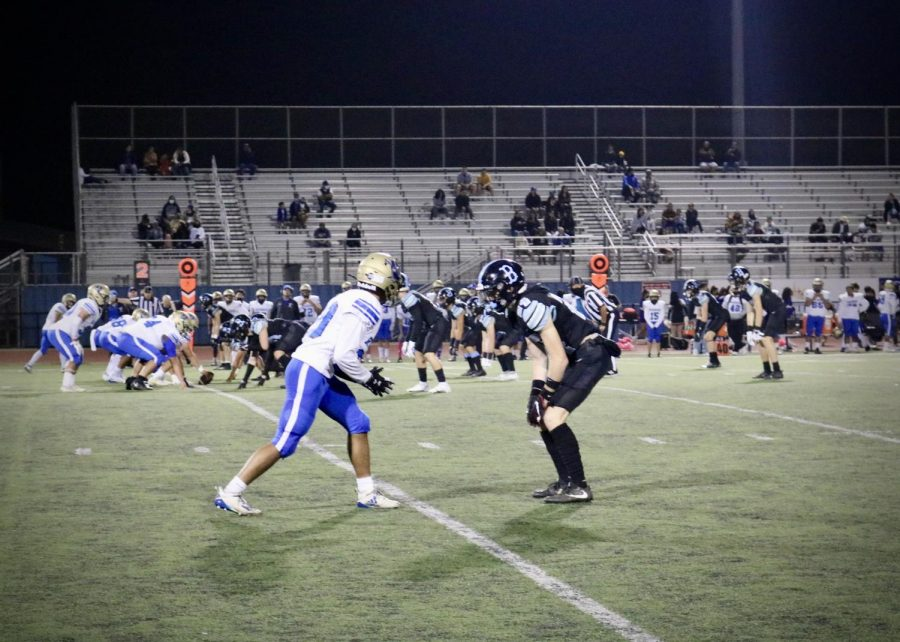 With the crowd cheering Junior Ty Morris takes the field to guard Channel Islands wide receiver before the snap.